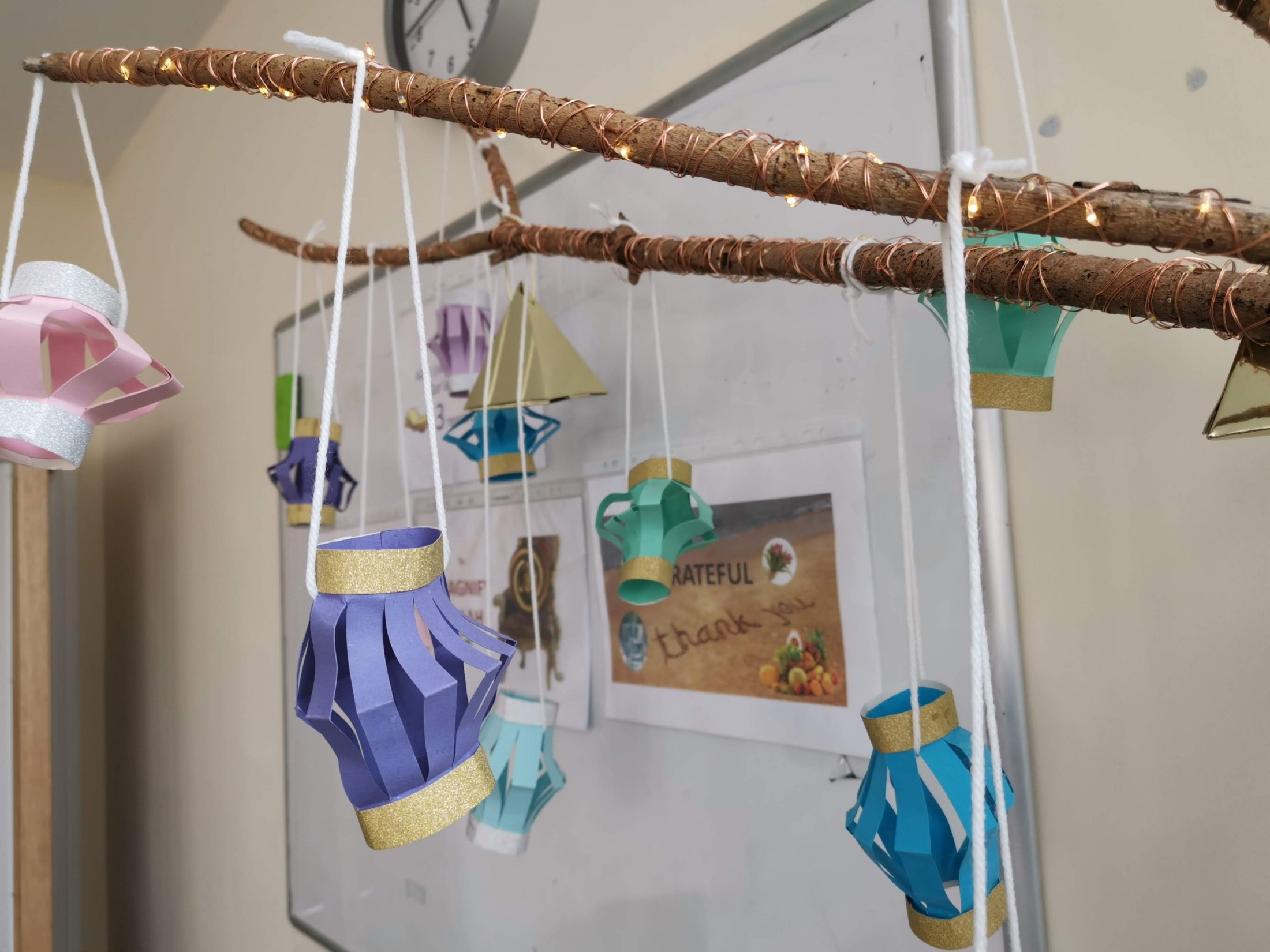 Paper lanterns hanging from a lit-up tree branch in one of our classrooms